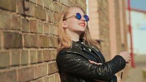 Blonde joven elegante en gafas de sol y chaqueta de cuero negra cerca de una pared de ladrillo en la calle metrajes