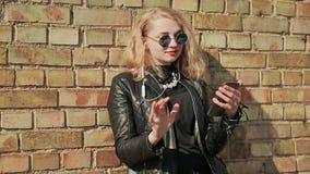 Blonde joven elegante en gafas de sol y la chaqueta de cuero que escucha la música en los auriculares del bluetooth en un teléfon almacen de video