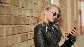 Blonde joven elegante en gafas de sol y la chaqueta de cuero que escucha la música en los auriculares del bluetooth en un teléfon almacen de metraje de vídeo