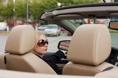 Blonde joven en un convertible Imágenes de archivo libres de regalías