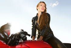 Blonde joven en una motocicleta roja grande Imagen de archivo