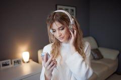 Blonde joven hermoso con los auriculares Selecciona la pista de la música en el app móvil, dentro Imagenes de archivo