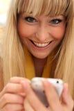 Blonde joven hermoso con un teléfono móvil Foto de archivo libre de regalías