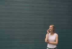 Blonde joven hermoso en la calle Inconformista femenino en un fondo gris usando un teléfono móvil lifestyle Foto de archivo libre de regalías