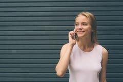 Blonde joven hermoso en la calle Inconformista femenino en un fondo gris usando un teléfono móvil lifestyle Imágenes de archivo libres de regalías