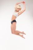 Blonde joven hermoso en un salto Imágenes de archivo libres de regalías