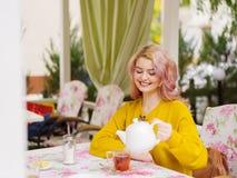 Blonde joven hermoso en un suéter amarillo en una tabla en un café Fotografía de archivo