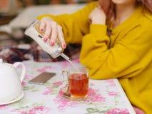Blonde joven hermoso en un suéter amarillo en una tabla en un café Fotos de archivo
