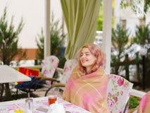 Blonde joven hermoso en un suéter amarillo en una tabla en un café Fotos de archivo libres de regalías