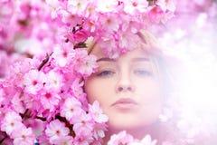 Blonde joven imponente en flores rosadas brillantes Foto de archivo libre de regalías
