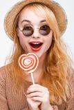 Blonde joven sorprendido en gafas de sol con la piruleta Foto de archivo libre de regalías
