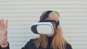 Blonde joven y elegante en vidrios virtuales en una pared blanca almacen de video