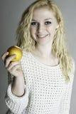 Blonde jugendlich Holding ein Apfel Lizenzfreie Stockfotografie