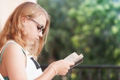 Blonde Jugendliche auf dem Balkon mit Buch Stockfotos