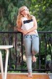 Blonde Jugendliche in den Gläsern steht auf Balkon Stockbilder