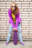 Blonde Jugendliche in den Jeans mit Skateboard Stockbilder