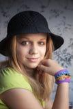 Blonde Jugendliche in den Webstuhlarmbändern des schwarzen Hutes und des Gummis Lizenzfreie Stockfotografie