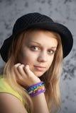 Blonde Jugendliche in den Webstuhlarmbändern des schwarzen Hutes und des Gummis Stockfotos