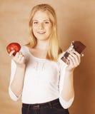 Blonde Jugendliche der jungen Schönheit, die das Schokoladenlächeln, Wahl zwischen Bonbon und Apfel isst Stockfoto