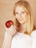 Blonde Jugendliche der jungen Schönheit, die das Schokoladenlächeln, Wahl zwischen Bonbon und Apfel isst Lizenzfreie Stockbilder