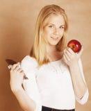 Blonde Jugendliche der jungen Schönheit, die das Schokoladenlächeln, Wahl zwischen Bonbon und Apfel isst Stockbild