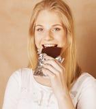 Blonde Jugendliche der jungen Schönheit, die Schokolade isst Stockfoto