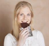 Blonde Jugendliche der jungen Schönheit, die Schokolade isst Lizenzfreie Stockfotografie