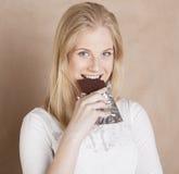 Blonde Jugendliche der jungen Schönheit, die Schokolade isst Lizenzfreie Stockfotos
