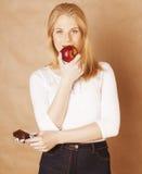 Blonde Jugendliche der jungen Schönheit, die Schokolade isst Stockbild