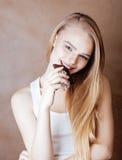 Blonde Jugendliche der jungen Schönheit, welche die lächelnde Schokolade, Lebensstilleutekonzept isst Stockfoto