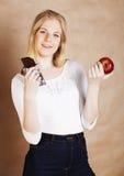 Blonde Jugendliche der jungen Schönheit, welche die lächelnde Schokolade, Wahl isst Lizenzfreie Stockfotografie