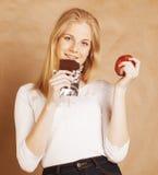 Blonde Jugendliche der jungen Schönheit, die das Schokoladenlächeln, Wahl zwischen Bonbon und Apfel isst Stockfotos