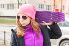 Blonde Jugendliche in der Sonnenbrille mit Skateboard Stockfoto