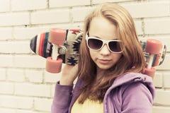 Blonde Jugendliche in der Sonnenbrille mit Skateboard Stockfotos