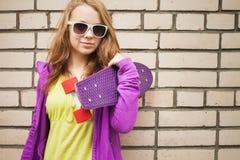 Blonde Jugendliche in der Sonnenbrille mit Skateboard Lizenzfreies Stockbild