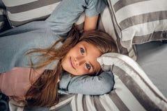 Blonde Jugendliche, die auf einer Couch liegt Lizenzfreie Stockbilder