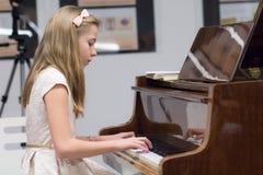 Blonde Jugendliche, die ein Klavier spielt Stockbild