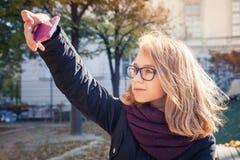 Blonde Jugendliche, die Foto auf ihrem Smartphone macht Stockfoto
