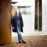 Blonde Jugendliche, die an Rusty Pier Support sich lehnt lizenzfreie stockfotografie