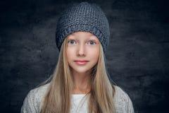 Blonde Jugendliche in einem warmen Winterhut Stockbild
