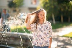 Blonde Jugendliche in einer blonden Bluse, die mit ihrem Haar auf dem Hintergrund eines Brunnens spielt Stockbild