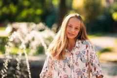 Blonde Jugendliche in einer blonden Bluse, die mit ihrem Haar auf dem Hintergrund eines Brunnens spielt Lizenzfreie Stockfotografie
