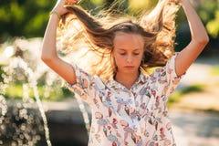 Blonde Jugendliche in einer blonden Bluse, die mit ihrem Haar auf dem Hintergrund eines Brunnens spielt Lizenzfreies Stockbild