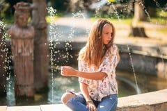 Blonde Jugendliche in einer blonden Bluse, die mit ihrem Haar auf dem Hintergrund eines Brunnens spielt Stockfotos