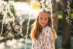 Blonde Jugendliche in einer blonden Bluse, die mit ihrem Haar auf dem Hintergrund eines Brunnens spielt Lizenzfreies Stockfoto