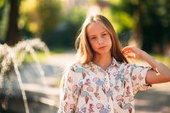 Blonde Jugendliche in einer blonden Bluse, die mit ihrem Haar auf dem Hintergrund eines Brunnens spielt Lizenzfreie Stockbilder