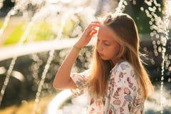 Blonde Jugendliche in einer blonden Bluse, die mit ihrem Haar auf dem Hintergrund eines Brunnens spielt Stockbilder
