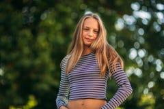 Blonde Jugendliche in gestreifter Bluse auf dem backgrountd des grünen Baums Lizenzfreie Stockfotos