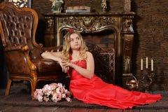 Blonde Jugendliche im hellen roten Kleid, das auf Lehnsessel sich lehnt Lizenzfreies Stockbild