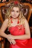 Blonde Jugendliche im hellen roten Kleid, das im Lehnsessel sitzt Lizenzfreie Stockbilder